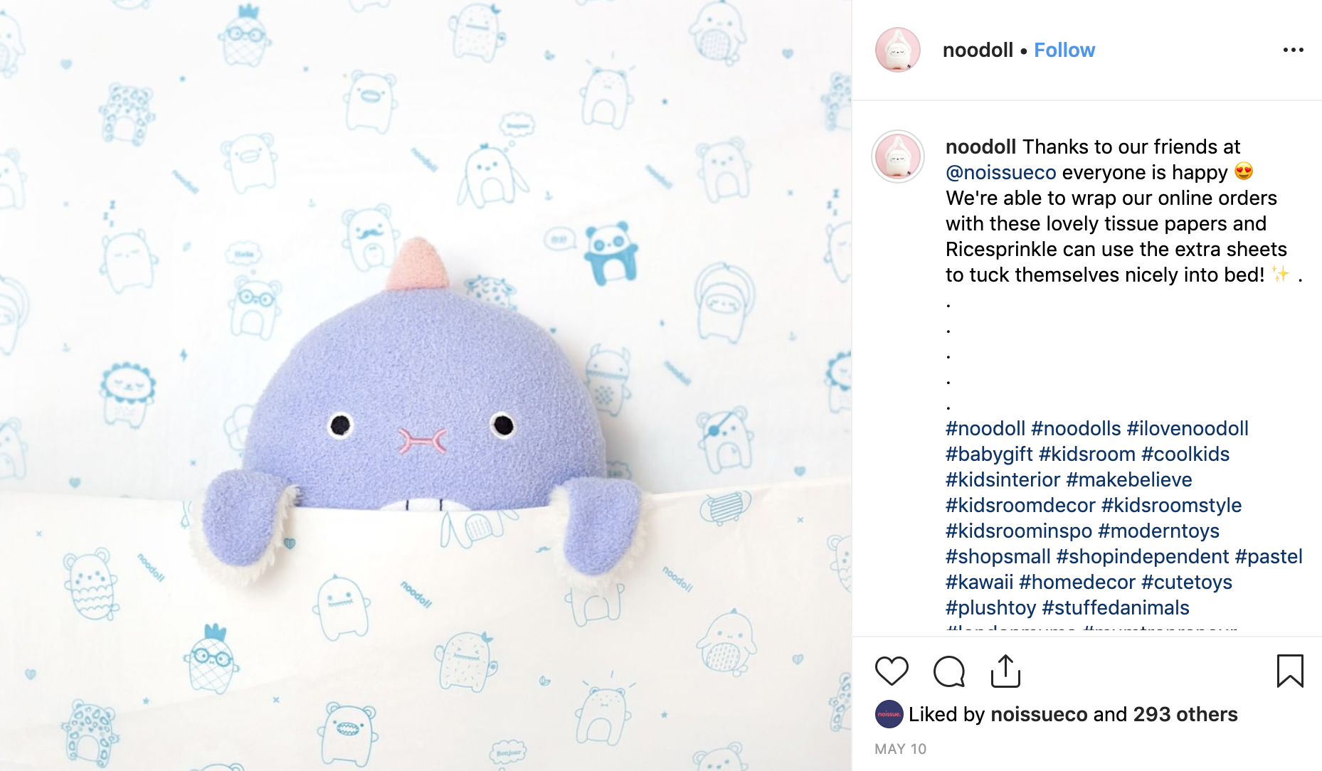 Noodoll toy tucked up in custom tissue paper like blankets
