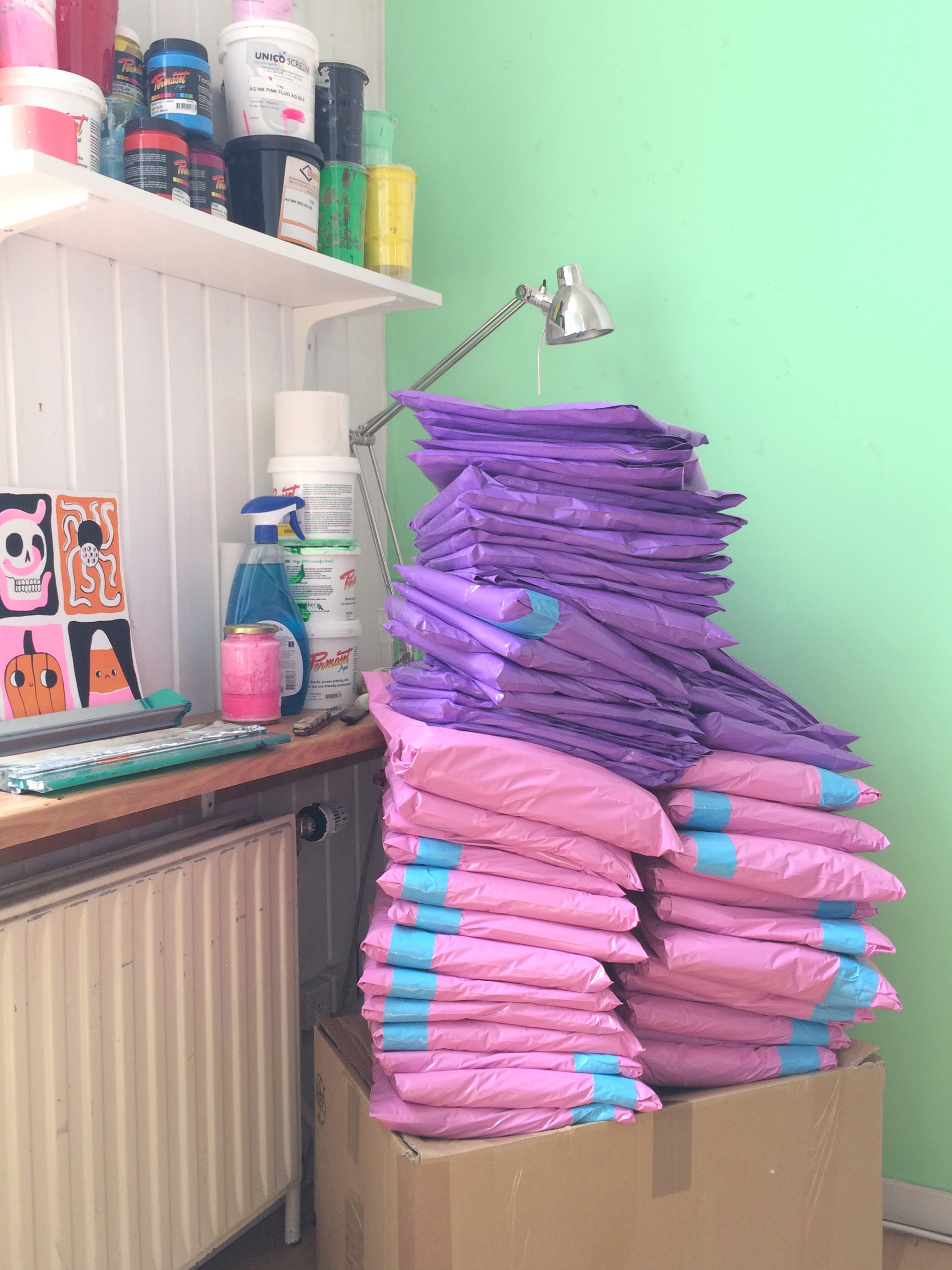 Pile of pink and purple mailer bags on desk